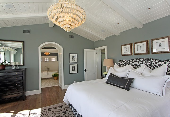grey comforter Bedroom with arched doorway baseboards ceiling finish carpentry
