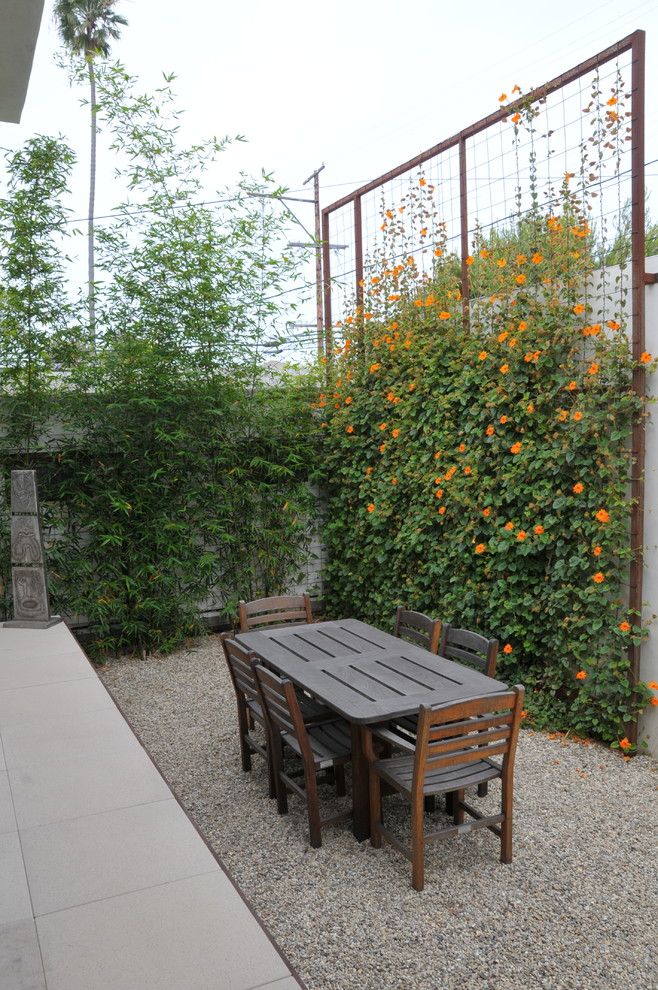 Iron Trellis Landscape Traditional with Bamboo Climbing Plants Gravel Patio Orange Flowers Outdoor Dining Chairs Outdoor Dining