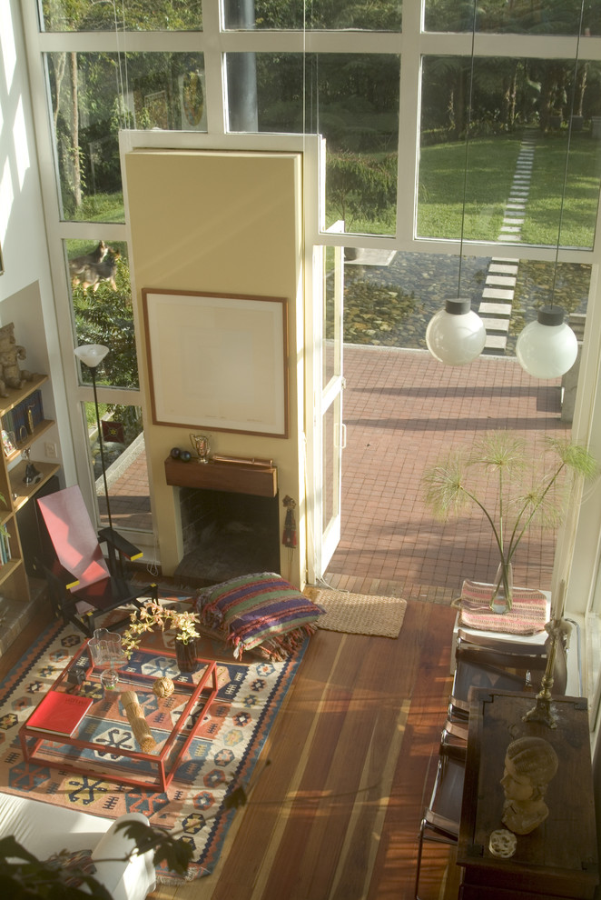 kilim rugs Living Room Eclectic with art arrangement breuer chair Fireplace glass coffee table glass house glass wall