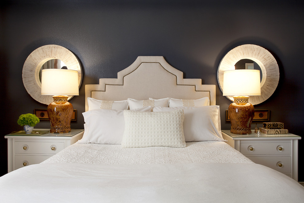 linen headboard Bedroom Contemporary with bedside table blue walls dark walls nailhead trim nightstand round mirrors table