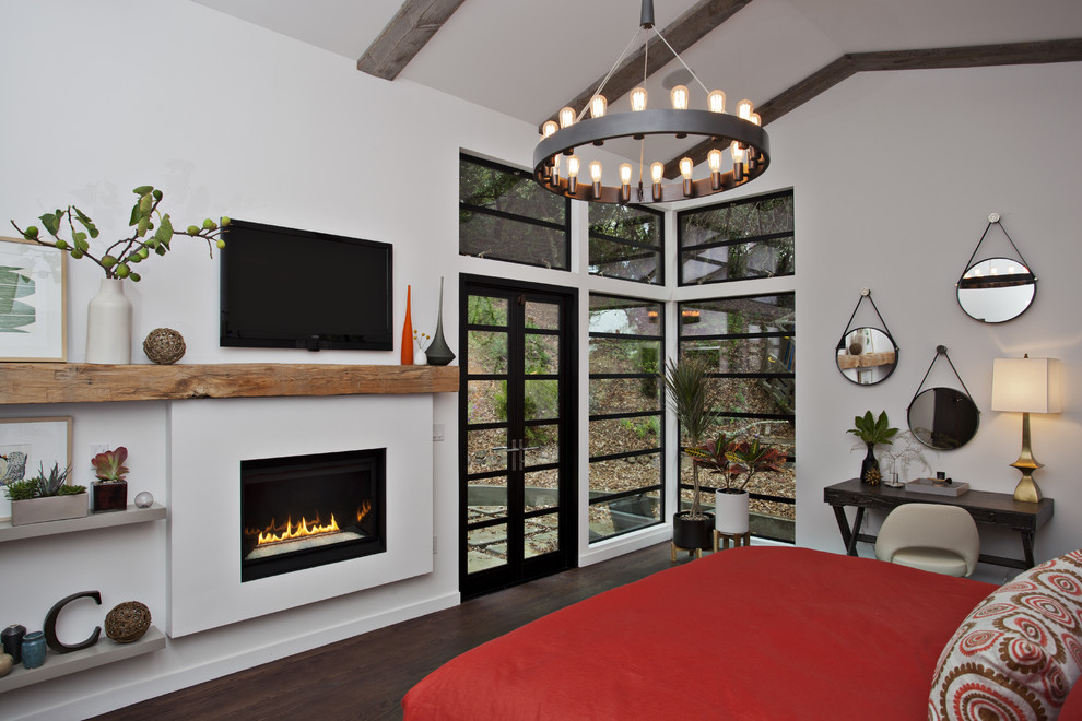 mantel fireplace Bedroom Contemporary with artwork beams chandelier dark stained wood floor desk chair Fireplace plants red