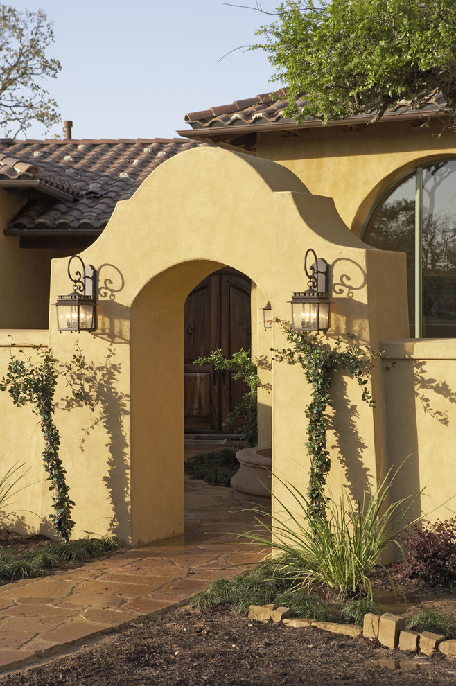 outdoor wall sconce Exterior Mediterranean with arched window courtyard entry iron work low wall stone walkway stucco tile