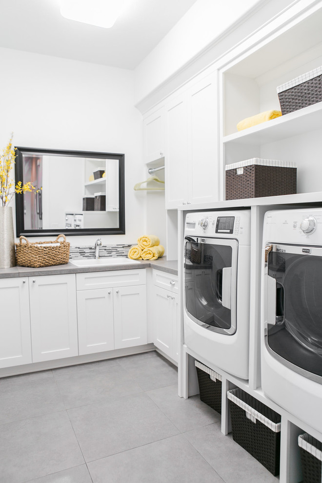 Portable Washing Machine and Dryer Laundry Room Transitional with Frame Mirror Gray Countertop Gray Tile Floor Open Shelves Storage Baskets Yellow