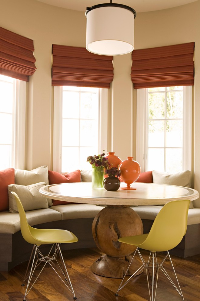 round pedestal table Dining Room Transitional with banquette breakfast nook centerpiece coral accent dark floor decorative pillows drum pendant