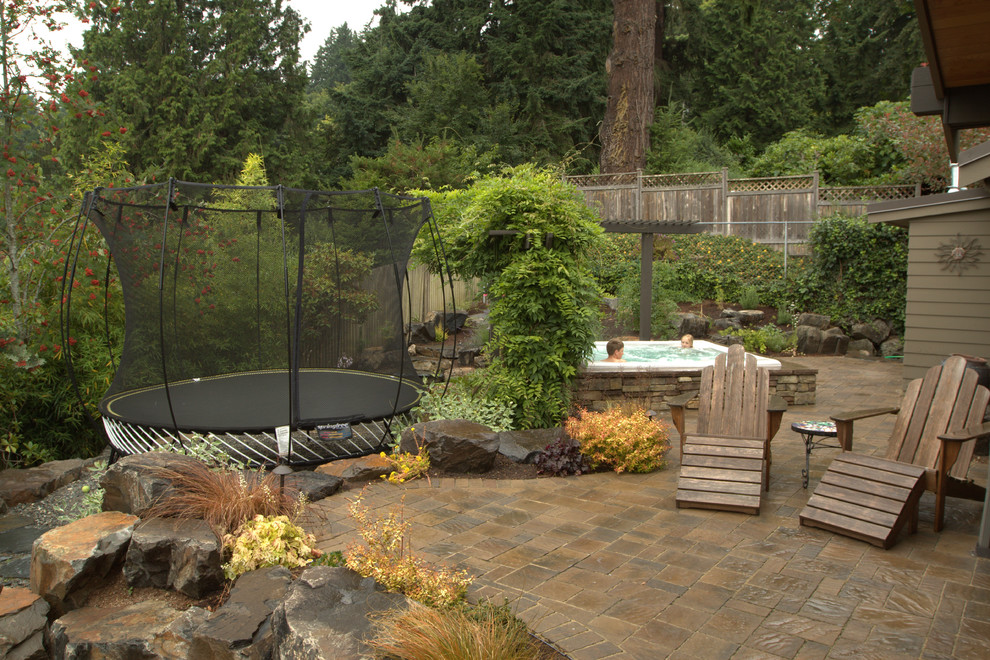 Trampoline with Enclosure Patio Traditional with Boulders Built in Hot Tub Built in Spa Bushes Red Flowers Rock Landscape Rocks