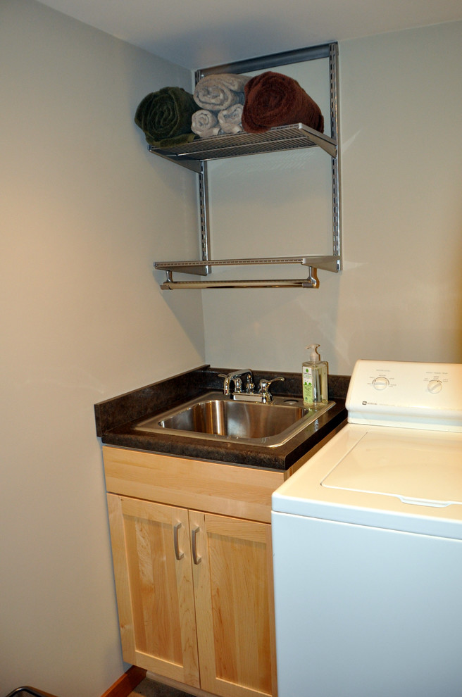 Utility Sink Cabinet Basement with Birch Cabinetry Chrome Fixtures Drain Tile Drying Racks Folding Station Laundry Room