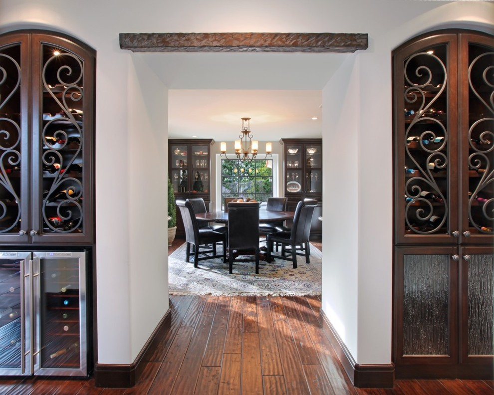 Wine Hutch Dining Room Mediterranean with Arch Area Rug Beverage Cooler Built in Cabinets Chandelier Dark Stained Wood Glass